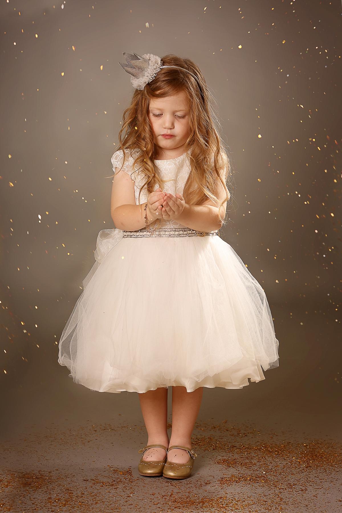 ילדה בלונדינית בשמלה לבנה על רקע מנצנץ