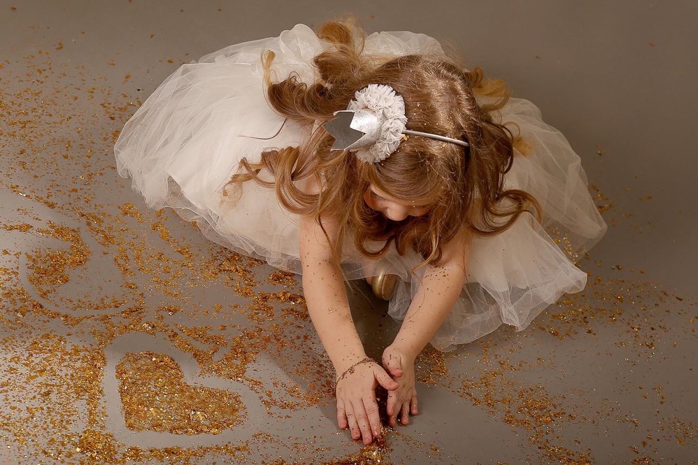 ילדה בלונדינית בשמלה לבנה עם נצנצים