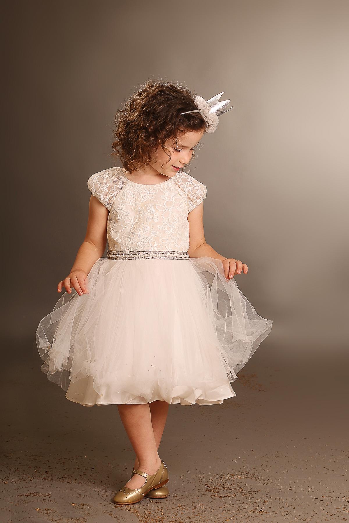 ילדה בשמלה לבנה מסתכלת על השמלה